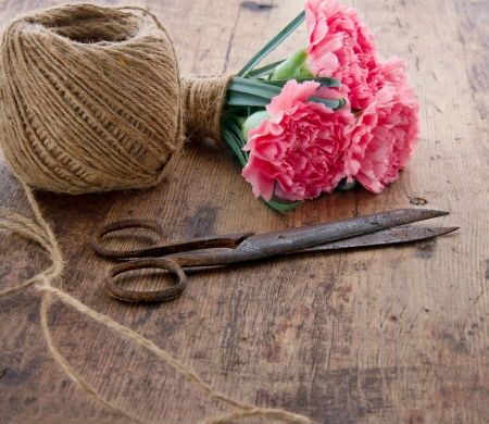 antique scissors: Bouquet of pink carnation flowers with old rusty antique scissors and ball of brown twine