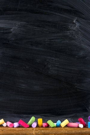 Black old empty chalkboard for copy space with colorful pieces of chalk Banco de Imagens