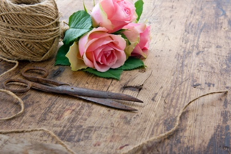 pink brown: Bouquet of pink rose flowers with old rusty antique scissors and ball of brown twine Stock Photo