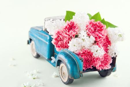 핑크 카네이션과 라일락 꽃을 들고 오래 된 골동품 장난감 트럭