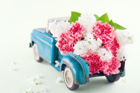 Old antique toy truck carrying pink carnation and lilacs flowers Stockfoto