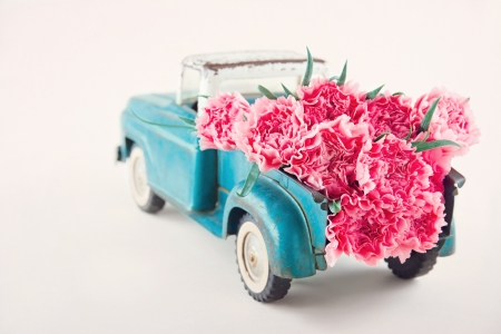 Old antique toy truck carrying pink carnation flowers Standard-Bild