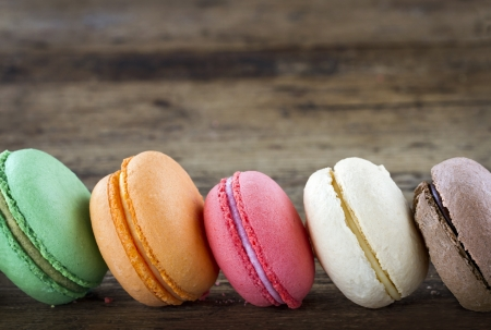 Row of colorful macaroons on wooden rustic background for copy space Stock Photo