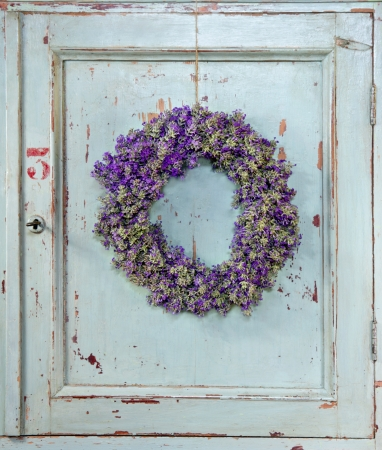 Lavender flower wreath hanging on an old wooden vintage kitchen door frame with copy space photo