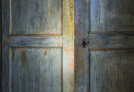 Green antique wooden door opening with light shining through