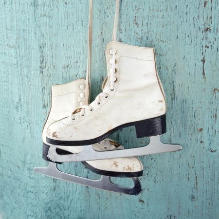 Pair of white womens ice skates on blue vintage wooden background - feminine winter sports concept
