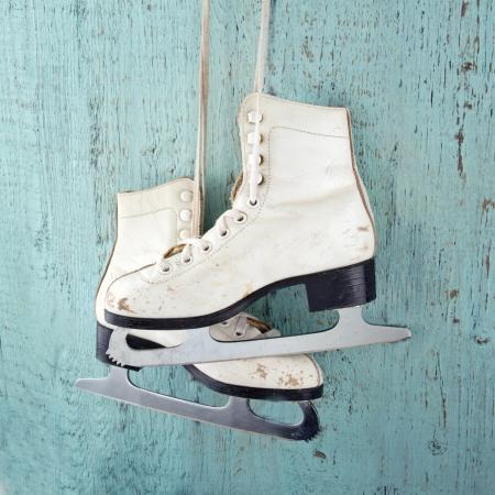 patinaje sobre hielo: Par de patines de hielo de las mujeres blancas en fondo azul de madera de la vendimia - femenino concepto de deportes de invierno