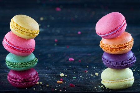 Two piles of colorful macaroons on a dark black wooden background with selective focus and small crumbs on the table
