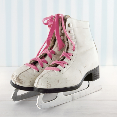 Pair of white womens ice skates on white and blue vintage background with pink shoe laces Stock Photo
