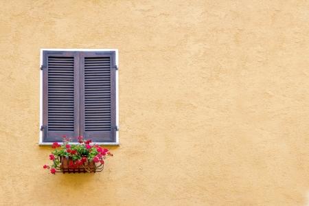 노란색 치장 용 벽 토 벽 및 복사 공간에 나무 셔터와 오래 된 창