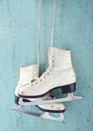 Pair of white women's ice skates on blue vintage wooden background - feminine winter sports concept