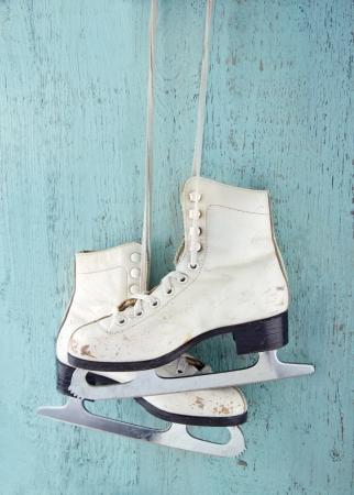 patinaje: Par de patines de hielo de las mujeres blancas en fondo azul de madera de la vendimia - femenino concepto de deportes de invierno