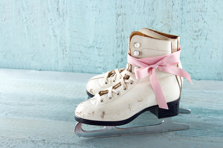 Pair of white womens ice skates on blue vintage wooden background with pink ribbon Stock Photo