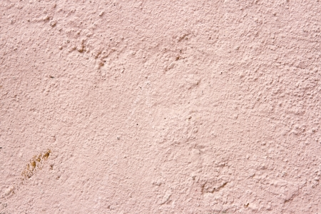 Plastered cream and pink color old cement wall background for copy space photo