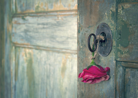 Green old wooden door opening with light shining through and red rose hanging from an old key Stockfoto