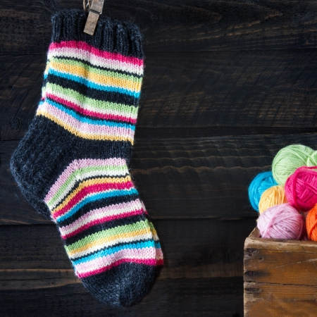 Pair of colorful striped woolen socks hanging on clothesline on dark wooden vintage background with multicolored balls of yarn and room for copy space photo