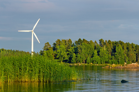 White wind turbine rotating in a sea shore green and blue landscape with evening sunlight and darks clouds - wind energy, sustainability and ecological concept background Stock Photo - 22558836