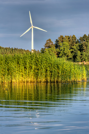 White wind turbine rotating in a sea shore green and blue landscape with evening sunlight and darks clouds - wind energy, sustainability and ecological concept background Stock Photo - 22558838