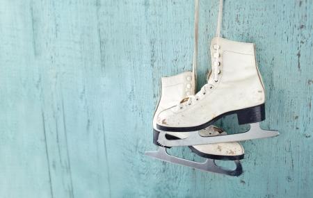 skating: Pair of white womens ice skates on blue vintage wooden background - feminine winter sports concept