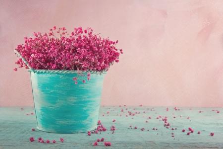 핑크 나무 빈티지 배경에 파란색 꽃병에 아기의 호흡 꽃을 건조