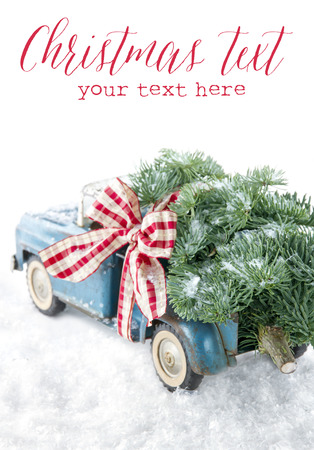 Old blue toy truck carrying a green Christmas tree covered with snow and a red ribbon on white snowy bakcground Stock Photo