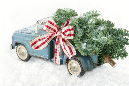 Old blue toy truck carrying a green Christmas tree covered with snow and a red ribbon on white snowy bakcground Stockfoto