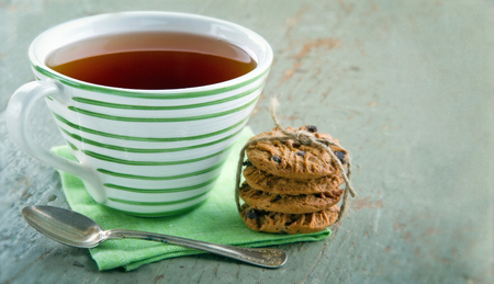 Closeup of chocolate chip cookies and a cup of tea on vintage wooden background photo