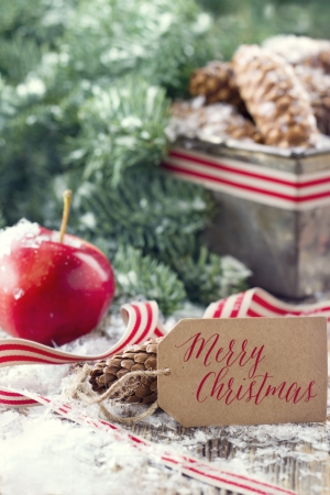 Brown pine cones and green spruce tree branches with snow in a decorative rustic Christmas setting on vintage wooden background photo