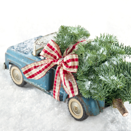 carrying: Old blue toy truck carrying a green Christmas tree covered with snow and a red ribbon on white snowy bakcground Stock Photo