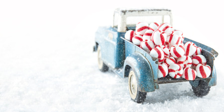 Old blue toy truck carrying striped peppermint candy on white snowy bakcground