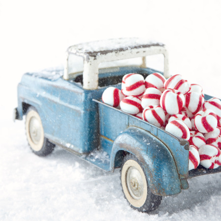 toy truck: Old blue toy truck carrying striped peppermint candy on white snowy bakcground