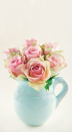 roses in vase: Pink roses in a light blue vase on cream beige shabby chic background with copy space