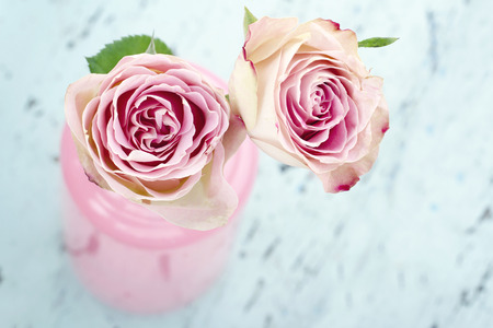 blue rose: Pink roses in a glass bottle on light blue wooden vintage background Stock Photo
