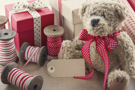Christmas present wrapping background, wooden vintage ribbons spools and gift boxes and and old teddy bear photo