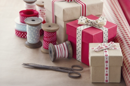 Christmas present wrapping background, wooden vintage ribbons spools and gift boxes and wrapping paper rolls Stockfoto