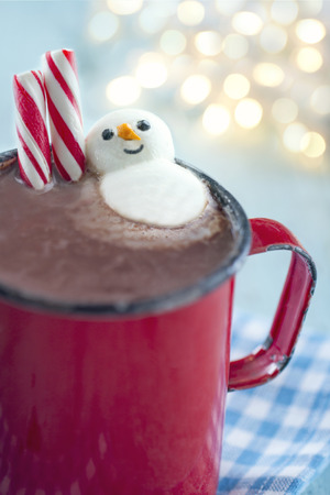Hot chocolate in a rustic red mug with candy canes and a marshmallow snowman on blue vintage background and bokeh lights photo
