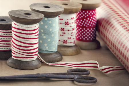 old spools: Wooden ribbon spools, paper rolls and old scissors for Christmas present wrapping on brown vintage background