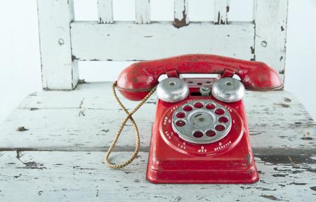 빛 푸른 나무 빈티지 의자에 빨간 장난감 전화