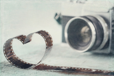 Heart shaped from film negative and old vintage camera - concept for photography
