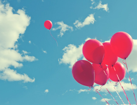 Bunch of red ballons on a blue sky with one balloon escaping to be individual and free - concept for following ones dreams Stock Photo