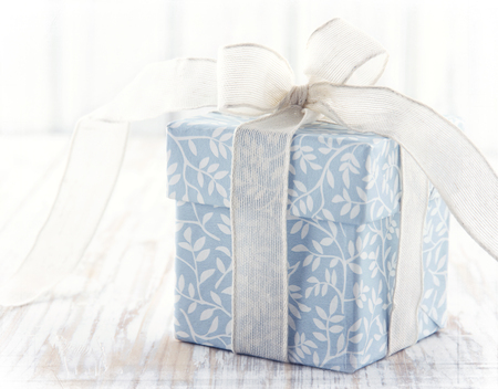 Light blue floral gift box tied up with white ribbon and pink flower on rustic wooden background Standard-Bild