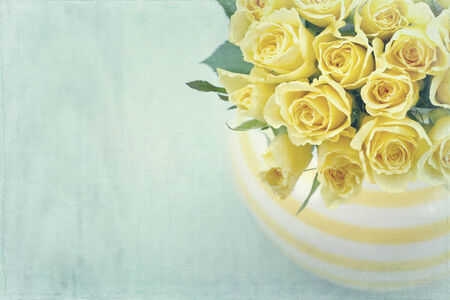 yellow roses: Striped vase with a bouquet of yellow spring roses on light blue vintage textured background Stock Photo