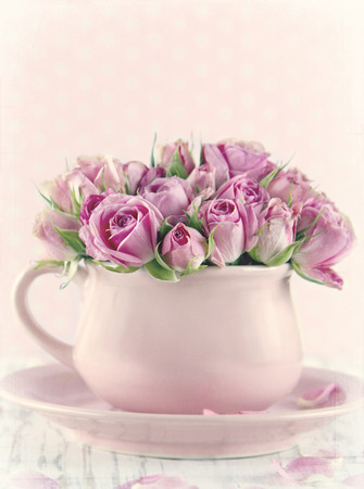 Bouquet of roses in a pink cup on wooden background with vintage textured editing
