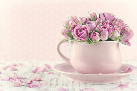 Bouquet of roses in a pink cup on wooden background with vintage textured editing Standard-Bild