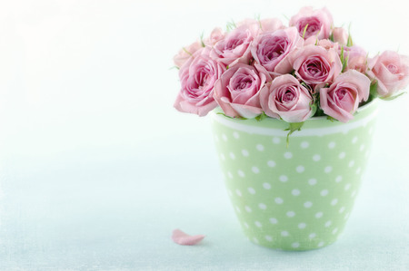 Romantic bouquet of roses in green cup on blue vintage background with textured editing Standard-Bild