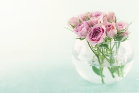 Roze rozen in een glazen vaas gevuld met wated op lichte blauwe achtergrond met vintage textuur bewerken Stockfoto