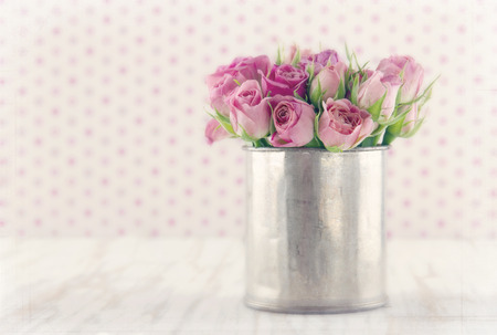 Romantic bouquet of roses in a metal tin cup on wooden vintage background with textured soft dreamy editing Stock Photo