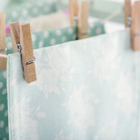 drying: Closeup of pastel color laundry drying on vintage wooden drying rack with copy space