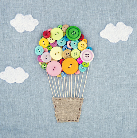 Handmade crafts of hot air balloon made of multicolored buttons on light blue linen textile background