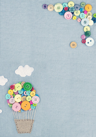 stitchwork: Handmade crafts of hot air balloon made of multicolored buttons on light blue linen textile background